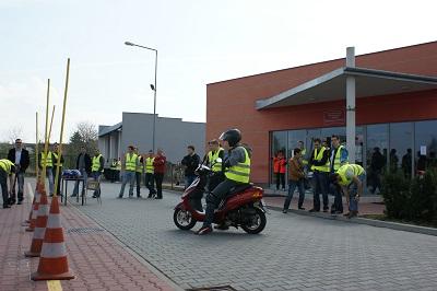 Osoba wykonująca na skuterze zadania treningowe. W tle grupa osób obserwująca co dzieje się na placu treningowym. Centrum BRD w Radomiu